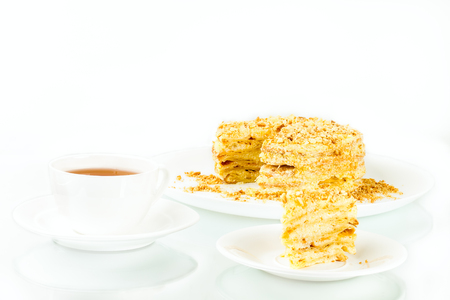cup of tea, puff homemade cake with custard and biscuit crumb on white background
