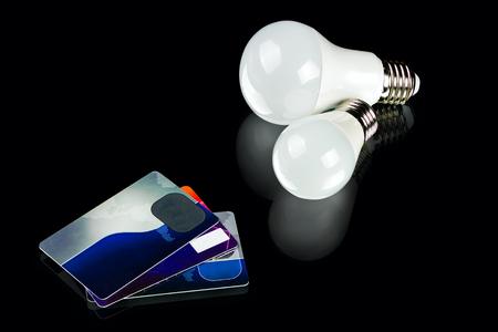 white innovation energy-saving LED bulb and credit cards on black background