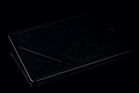 graphic tablet with pen on black background, low-key