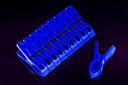 blue new plastic clothespins on dark background