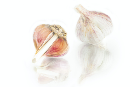 fresh nice garlic cloves and garlic bulb with reflection on white background Фото со стока