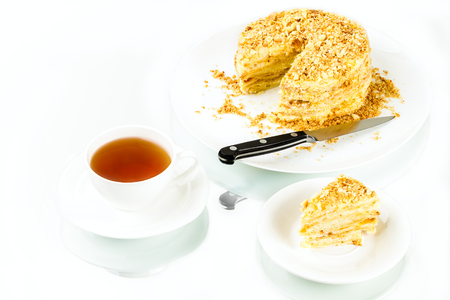 cup of tea, knife, puff homemade cake with custard and biscuit crumb on white background Фото со стока