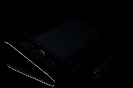 Graphic tablet with pen on black background, low-key Фото со стока