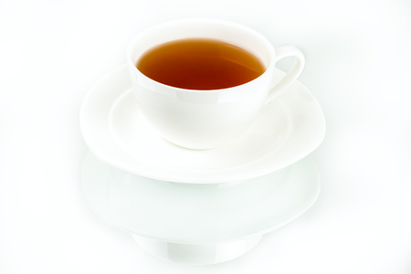 white ceramic saucer with cup of tea on white background