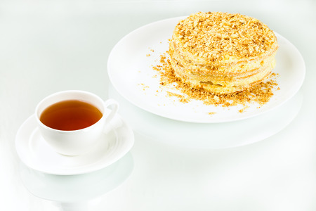 cup of tea, puff homemade cake with custard and biscuit crumb on white background Фото со стока - 98892343