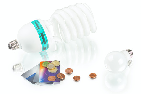 innovation energy-saving LED bulb, spiral lamp and coins on white background