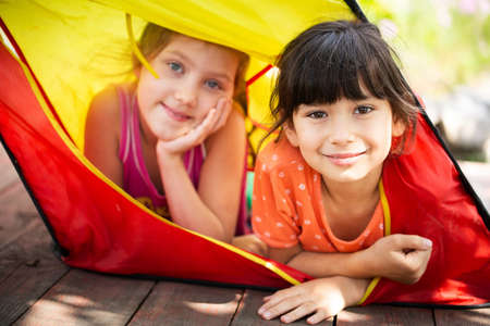 Joyful children in the summer camp. Schoolchildren near the tent on a sunny day. Summer vacation in nature.