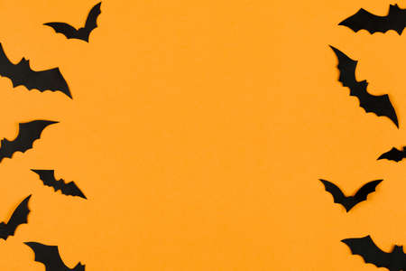 halloween decorations concept, many black paper bats on orange background, table top view, lots of free space