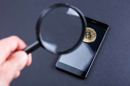 coin bitcoin under a magnifying glass on a dark background, extraction of crypto currency