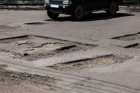 repair works are being carried out, road repairs in Ukraine, a big hole on the road asphalt result of military operations 版權商用圖片