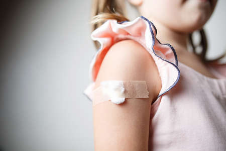 little girl with plaster on the shoulder from the injection, vaccinated in the shoulder, child vaccination, treatment of children patch Banque d'images - 130477569