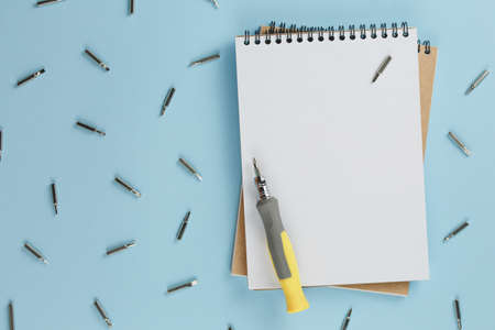 masters desk with a blank notebook and a set of hand tools on a blue background, a set of screwdrivers