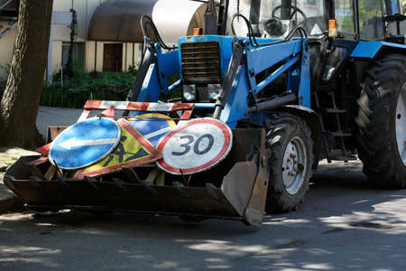 tractor stands on the road with loaded signs, a road repair technician