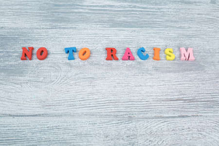 No to racism in colored letters on a gray wooden background, black and white pawn, the concept of the struggle for freedom of human rights 스톡 콘텐츠