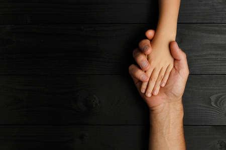 Draufsicht, Erwachsene Hände, die Kinderhände halten, Family Help Care Concept, kleine Hände in der Hand des Vaters. auf schwarzem Holzuntergrund