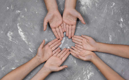 childrens hands together in a circle with their hands up on a gray background, top view. joint support and assistance in the community