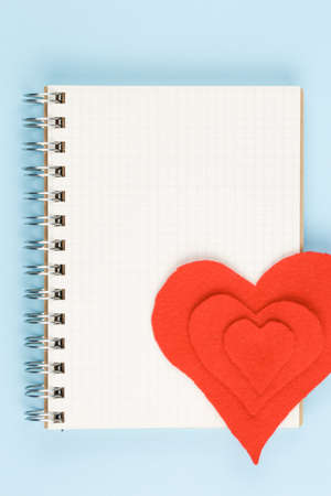 red heart on open notebook on blue background top view, symbol of love, peace, health and help to those in need vertical view