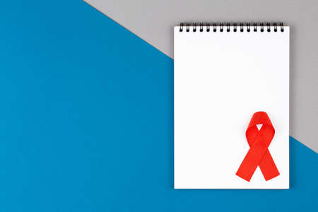 red aids ribbon on open notebook isolated on blue and gray background, aids day and symbol of helping cancer patients vertical view