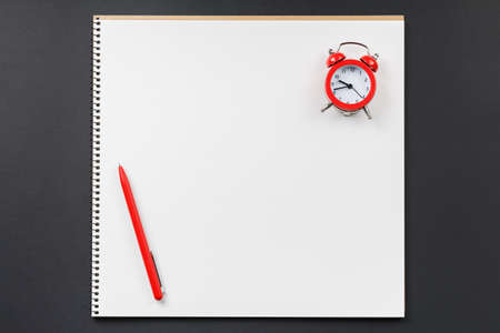 open notebook with red alarm clock on black background top view, school notepad on a dark table, office desk flat lay Banco de Imagens