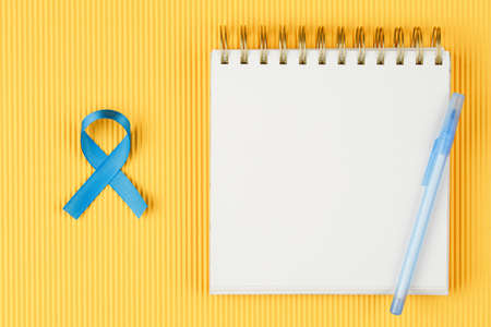 blue prostate ribbon on open notebook isolated on yellow background, prostate cancer and symbol of helping HIV patients