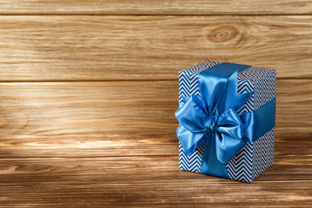 Gift box with blue ribbon on wooden background top view. New year and Christmas holiday concept. Flat lay with copy space. Discount gift for sale day.