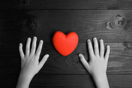 red heart in hands on a dark background, the concept of love and care for loved ones and needy.black and white.