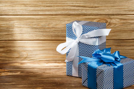 Many gifts box with ribbon on wooden background top view. New year and Christmas holiday concept. Flat lay with copy space. Discount gift for sale day.
