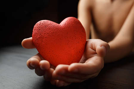 red heart in hands on a dark background, the concept of love and care for loved ones and needy