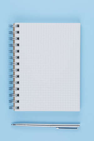 school notebook with pen on a blue table top view, office desktop, office supplies on a light blue background Stock fotó