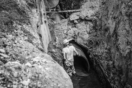 replacement of a sewer pipe deep under the ground, laying pipes under the ground, construction of a water supply line, repair of sanitary ware in Ukraine.black and white.