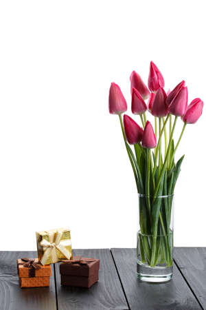 pink tulips in a glass on an isolated white background, tulips on a table, a festive bouquet Banco de Imagens