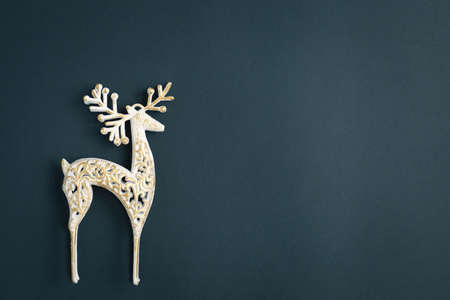 Christmas and New Year background with gifts, deer, stars and fir-trees, flat lay on a dark blue background, holiday greetings, concept of a winter background with free space