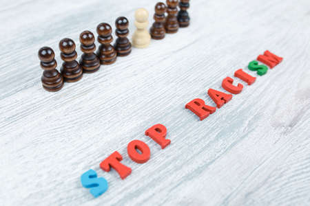 No to racism in colored letters on a gray wooden background, black and white pawn, the concept of the struggle for freedom of human rights Stock Photo