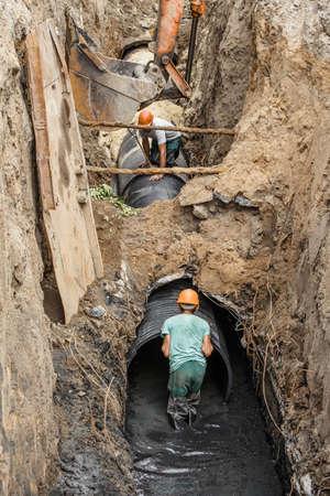 remplacement d'un tuyau d'égout en profondeur, pose de tuyaux sous terre, construction d'une conduite d'alimentation en eau, réparation d'appareils sanitaires en Ukraine Banque d'images