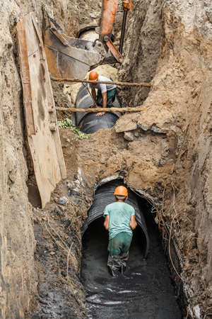 replacement of a sewer pipe deep under the ground, laying pipes under the ground, construction of a water supply line, repair of sanitary ware in Ukraine Stockfoto