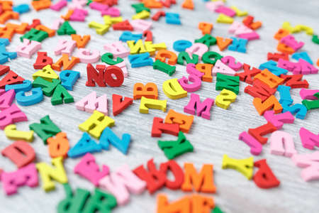 colored wooden letters on a gray wooden background, English letters painted in different colors, a day of knowledge