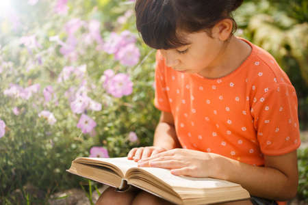 Cute girl in T-shirt is reading outdoors on an sunny day. Preparation for school and international literacy day. Back to school concept.