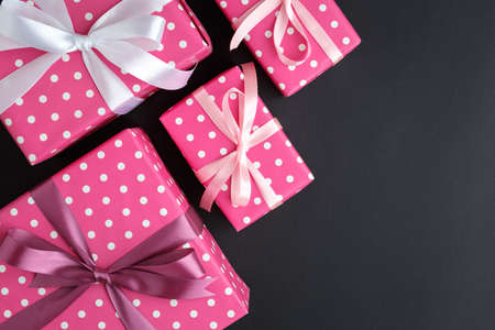 gifts on a dark background lined, top view on a gift box, flat lay
