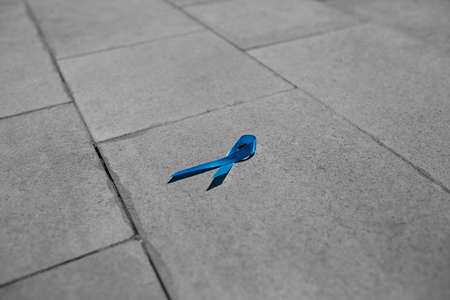 blue ribbon on a gray stone, prostate cancer awareness. male disease