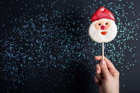 candy on a stick in the hand in the form of a santa, on a dark background with the stars
