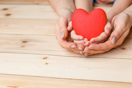 hands with red heart, top view on white and wooden background
