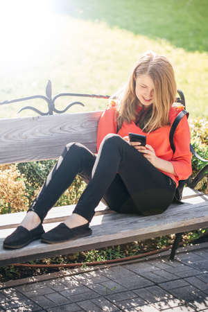beautiful teenage girl with a backpack correspond with friends in social networks through a smartphone, a girl travels through Europe on a sunny day