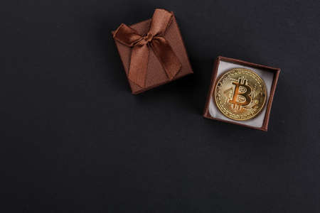 coin bitcoin in a gift box on a dark background, crypto currency as a gift