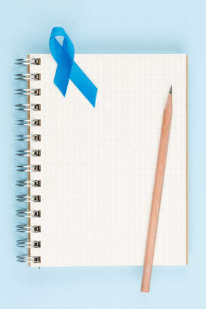 blue prostate ribbon on open notebook isolated on blue background, prostate cancer and symbol of helping HIV patients Stock Photo