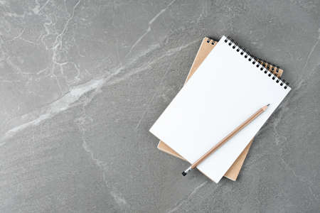 School notebook on the marble table top view.business concept