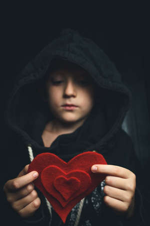 child with a red heart on a dark background. the boy holds the symbol of good and life. concept of helping those in need