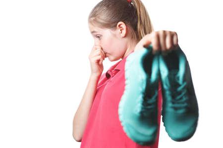 Mädchen hält stinkende Turnschuhe und schließt ihre Hand mit der Nase, Geruch von Schuhen, Foto auf weißem, isoliertem Hintergrund