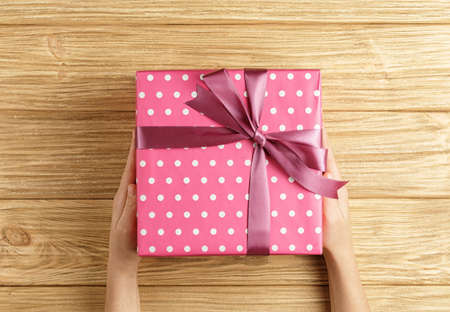 gift box in the hands on a wooden background top view, flat lay festive concept, female hands with pink box with a gift Stock Photo