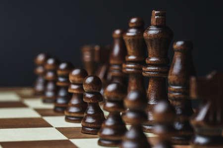 pièces d'échecs sur un échiquier, sur un fond sombre. Les chiffres noirs se tiennent dans une rangée, le concept de stratégie de réussite et le bon choix Banque d'images