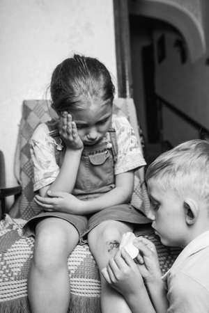 A little girl hurt her knee, a boy heals her wound. a scratched knee. brave girl.black and white. Standard-Bild - 133664256